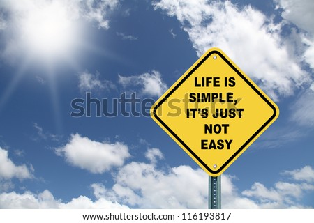 Yellow cautionary road sign Life is Simple, it's just not Easy against a blue sky - stock photo