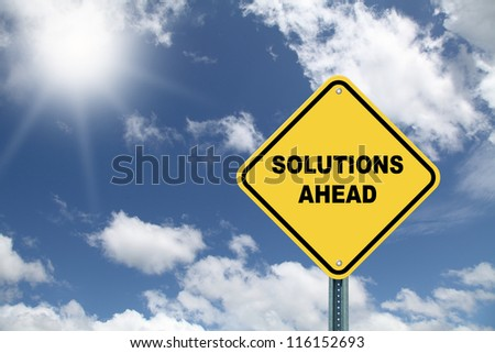 Yellow cautionary road sign Solutions Ahead against a beautiful sky background - stock photo