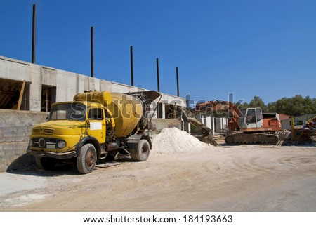 Yellow cement mixer truck and digger - stock photo
