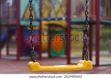 Yellow chain swings on modern kids playground with shallow depth of field - stock photo