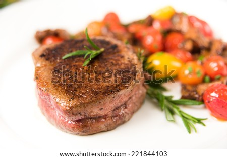 Yellow Chanterelle Mushrooms Cooked in Butter and Wine with Cherry Tomatoes Served with Medium Rare Filet Mignon - stock photo
