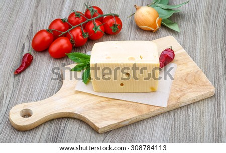 Yellow cheese brick with mint leaves on the wood background - stock photo