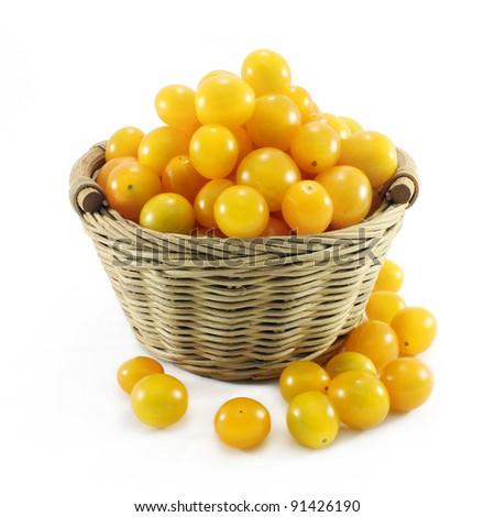 Yellow cherry tomatoes in rattan basket - stock photo