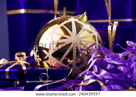 yellow Christmas ball,violet Christmas boxes against blue background ,yellow and violet ribbon  - stock photo