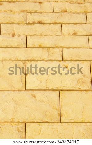 Yellow cladding tiles imitating stones in sunny day  - stock photo