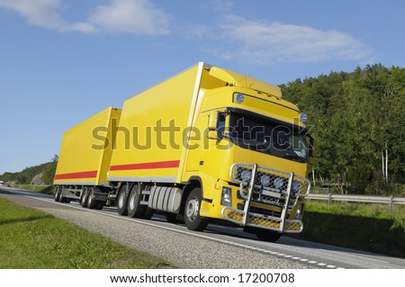yellow clean truck driving on scenic highway, tilted perspective, trademarks removed, red stripes are standards. - stock photo
