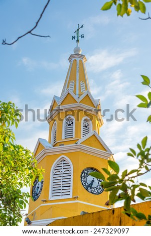 Yellow clock tower marking the main entrance into the historic old town of Cartagena, Colombia - stock photo
