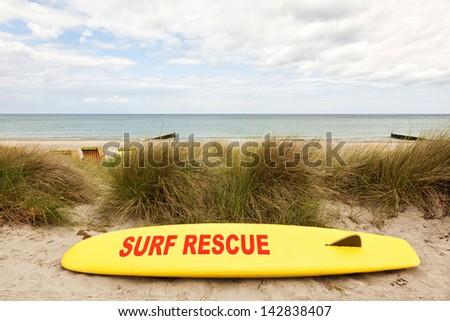 Yellow coast guard rescue surfboard at the baltic sea beach - stock photo