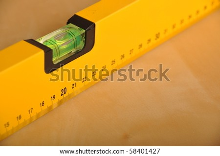 yellow construction level on a brown wooden background - stock photo