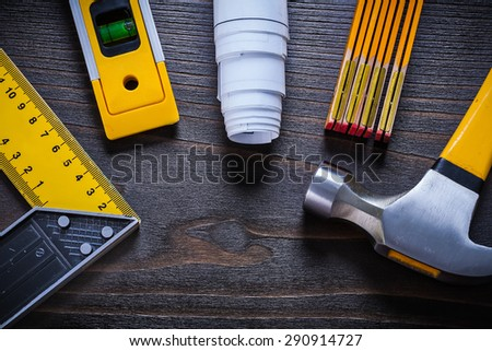 Yellow construction level try square rolled up white blueprint wooden meter and hammer on vintage wood surface maintenance concept. - stock photo