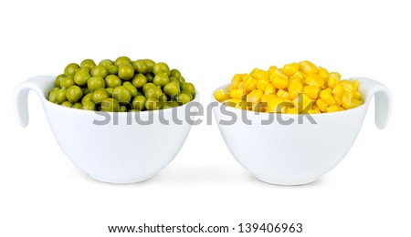 Yellow corn grains and freshly shelled green peas a white dishes over white background - stock photo