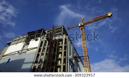 Yellow Crane and building construction site against blue sky - stock photo