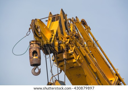 Yellow crane arm with hook close-up - stock photo