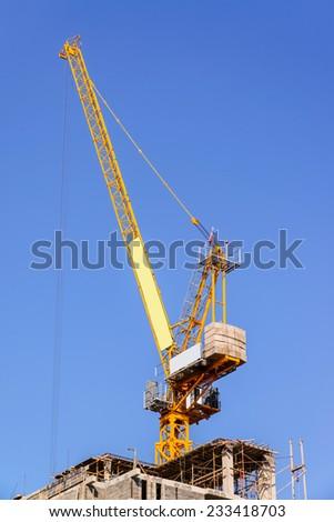 Yellow crane isolate on blue sky background  - stock photo
