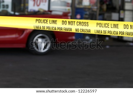 Yellow crime scene tape surrounds gas station - stock photo