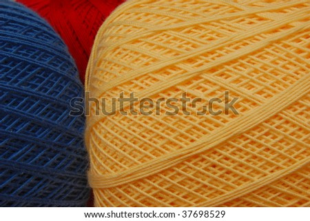 Yellow crochet thread with blue and red in the background - stock photo