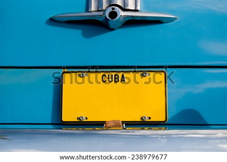Yellow Cuban Plate on Blue Car - stock photo