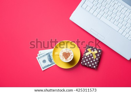 yellow cup of coffee, gift, money and laptop on the red background - stock photo