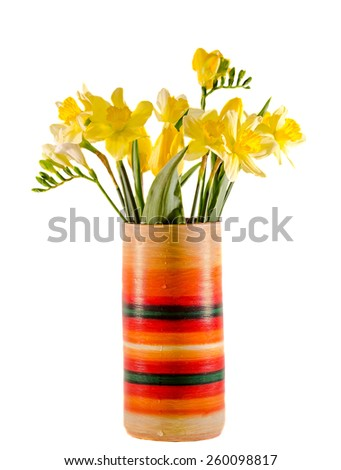Yellow daffodils and freesias flowers in a vivid colored vase, close up, isolated, white background. - stock photo