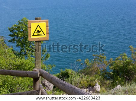 Yellow Danger Sign over the Wooden Fence of a Seaside Panoramic Trail - stock photo