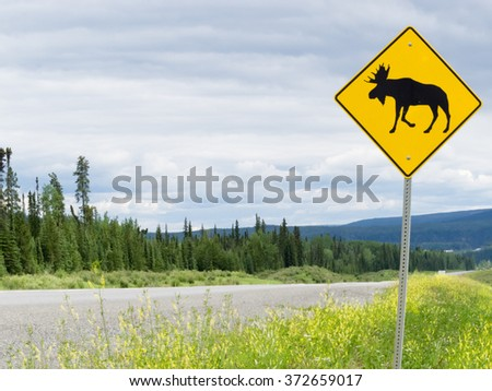 Yellow diamond traffic road sign warning, Attention moose crossing, posted alongside a scenic rural country road in lush countryside - stock photo