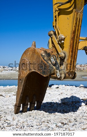 Yellow diggers on the seashore building a breakwater - stock photo