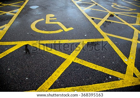 Yellow disable parking road sign marking on tarmac - stock photo