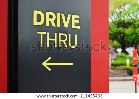 yellow drive thru text with arrow - stock photo