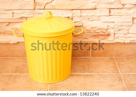 Yellow dustbin on the floor with brick wall behind - stock photo