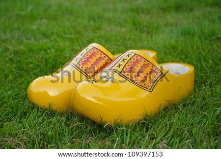 Yellow Dutch traditional wooden shoes on grass. - stock photo