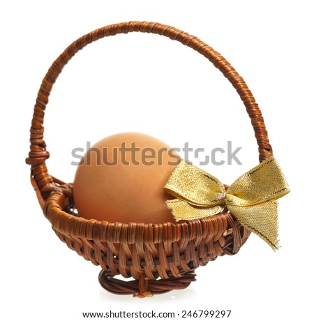 Yellow egg in the wicker basket isolated on white background - stock photo