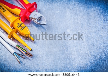 Yellow electrical tester wires nippers on metallic background copy space electricity concept. - stock photo