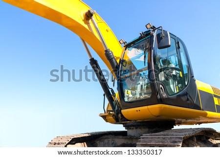 Yellow excavator at construction site - stock photo