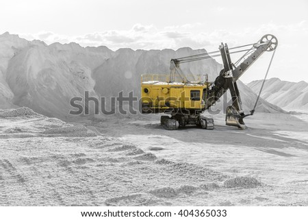 Yellow excavator standing among the rubble mountains in the black-and-white background - stock photo