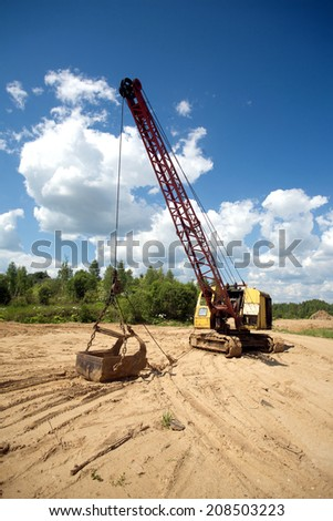 Yellow excavator with big heavy bucket standing on sand on background of forest and blue sky with white clouds on summer day vertical view - stock photo
