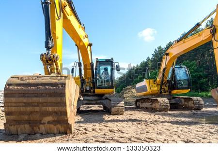 Yellow excavators on a construction site - stock photo
