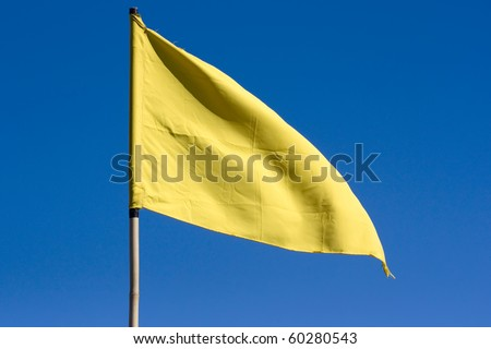 Yellow flag with blue sky - stock photo