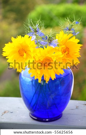 yellow flowers in a blue vase - stock photo