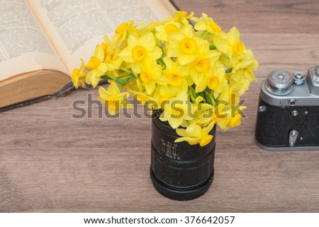 Yellow flowers in old lens, vintage camera and book on a wooden table. - stock photo