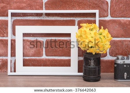 Yellow flowers in old lens, vintage camera and empty white photo frames on a background of red brick wall. - stock photo