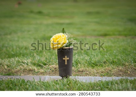 Yellow flowers set at graveside in memorial cemetery in California. - stock photo