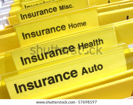 Yellow folders show different types of insurance papers - stock photo