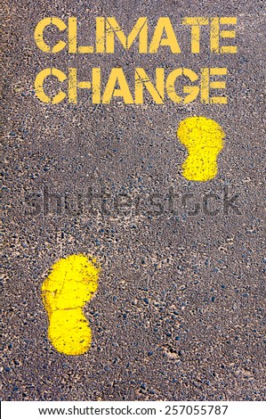 Yellow footsteps on sidewalk towards Climate Change message.Conceptual image - stock photo