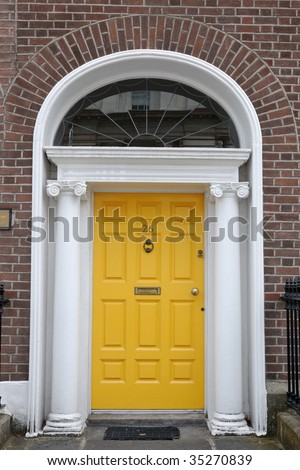 Yellow  front door in classic urban street - stock photo
