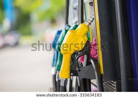 Yellow fuel nozzle at a gas station. - stock photo