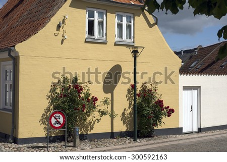 Yellow gable with traffic sign, lamp and red roses from Middelfart, Denmark. - stock photo