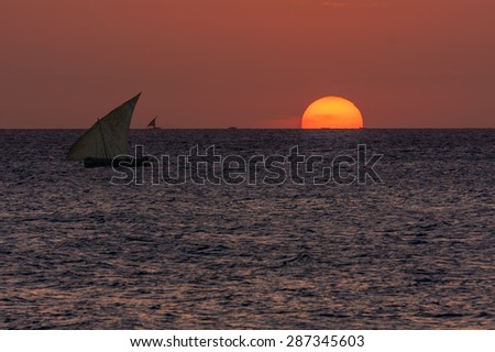 yellow glow of the rising or setting sun over a textured ocean showing the yellow orb of the sun on the horizon and the traditional african dhow - stock photo
