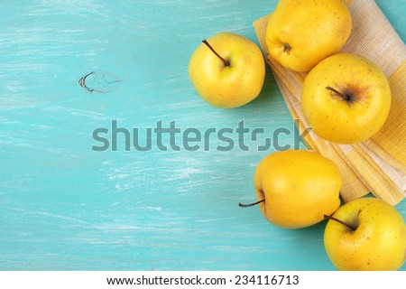 Yellow Golden Delicious apples with linen napkin on turquoise rustic wooden table. Top view point. - stock photo