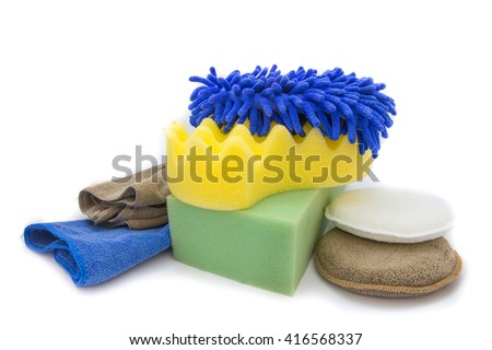 Yellow, green sponges and blue mitts for washing and microfiber fabric with cleaner cloth on white background - stock photo