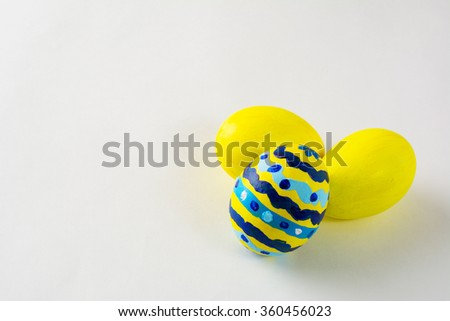 Yellow hand- decorated Easter eggs with abstract design on a white background. Easter background. Easter symbol. Copy space - stock photo